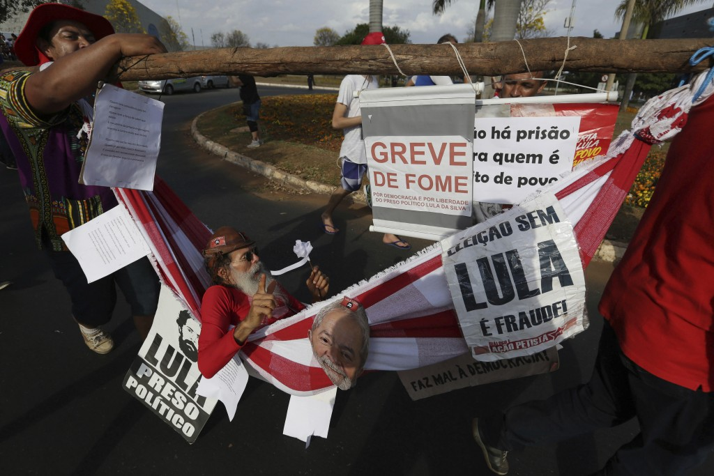 A supporter of Brazil's jailed, former President Luiz Inacio Lula da Silva is carried in a hammock while he is on hunger strike to protest the former ...