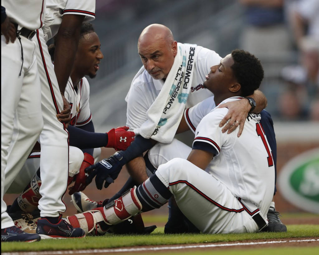Atlanta Braves' Ronald Acuna Jr. (13) is tended to by a member of the training staff as Ozzie Albies talks to him after Acuna was hit by a pitch from ...