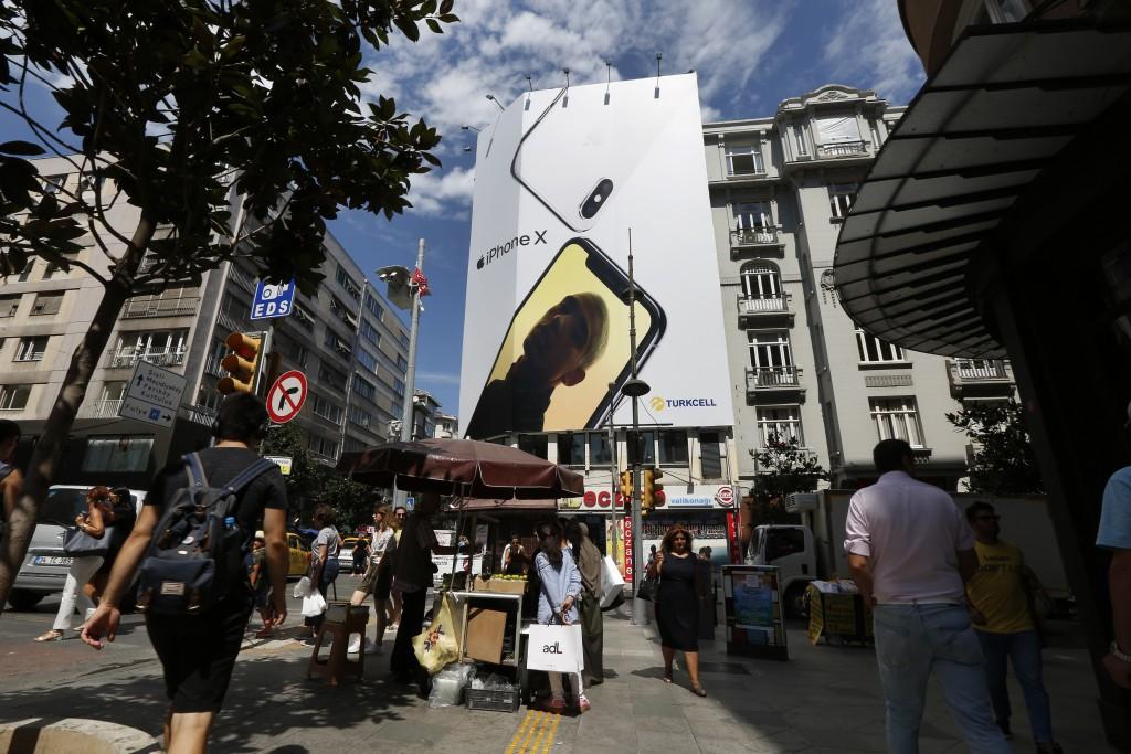 People walk past an advertising billboard for a smartphone in an upscale neighborhood in Istanbul, Turkey, on Wednesday, Aug. 15, 2018. Haydar Tastan,...