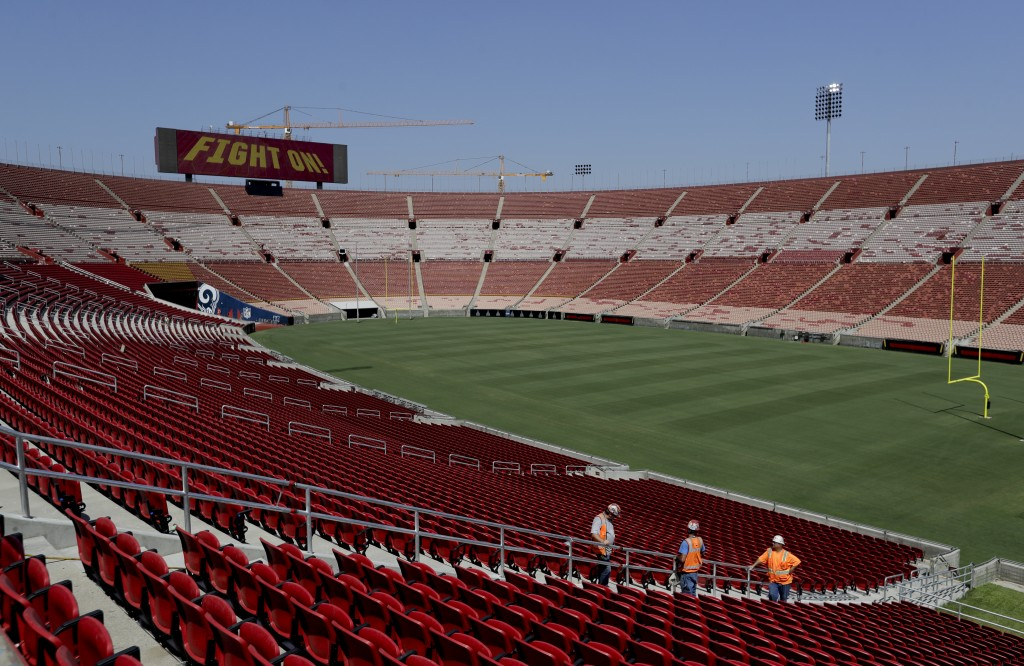 Stadium personnel walk near a new section of seats at the Los Angeles Memorial Coliseum in Los Angeles, Wednesday, Aug. 15, 2018. The 95-year-old Coli...