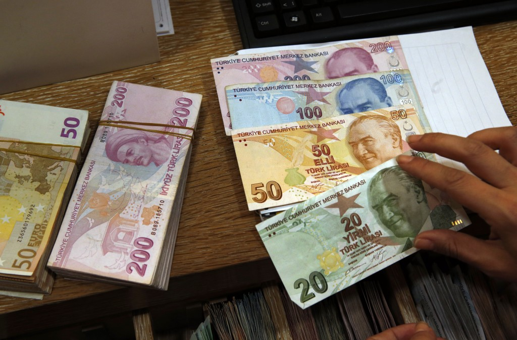 A worker at a currency exchange shop worker lays out Turkish lira banknotes depicting modern Turkey's founder Mustafa Kemal Ataturk, in Istanbul, Wedn...
