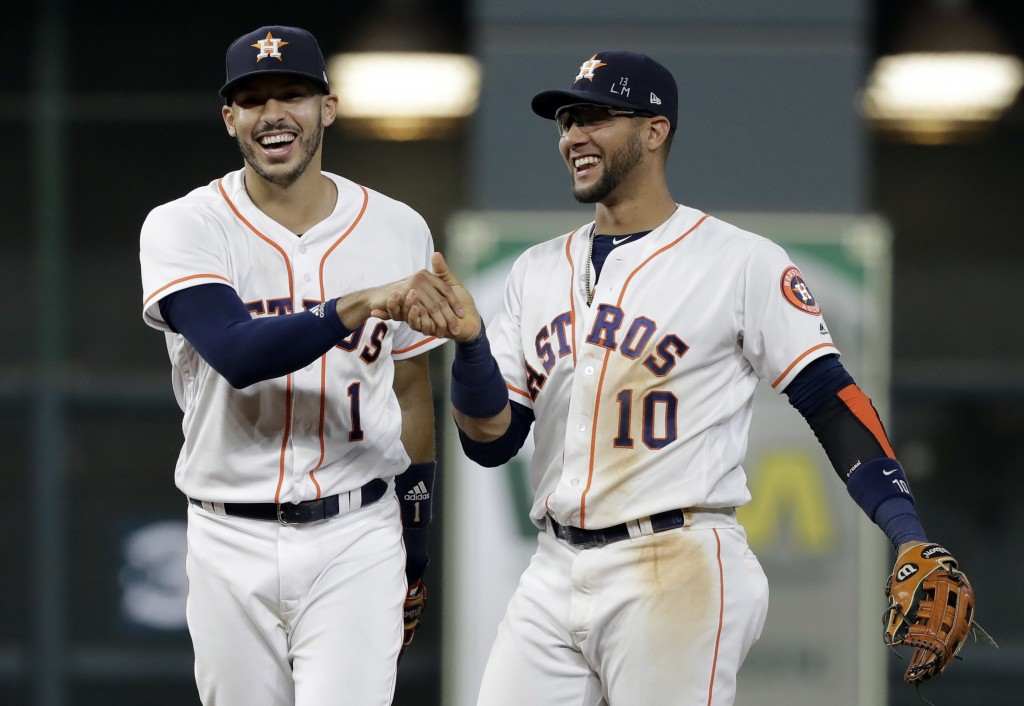 Houston Astros shortstop Carlos Correa (1) reacts with second baseman Yuli Gurriel (10) after fielding a ground ball by Colorado Rockies' Tony Wolters...