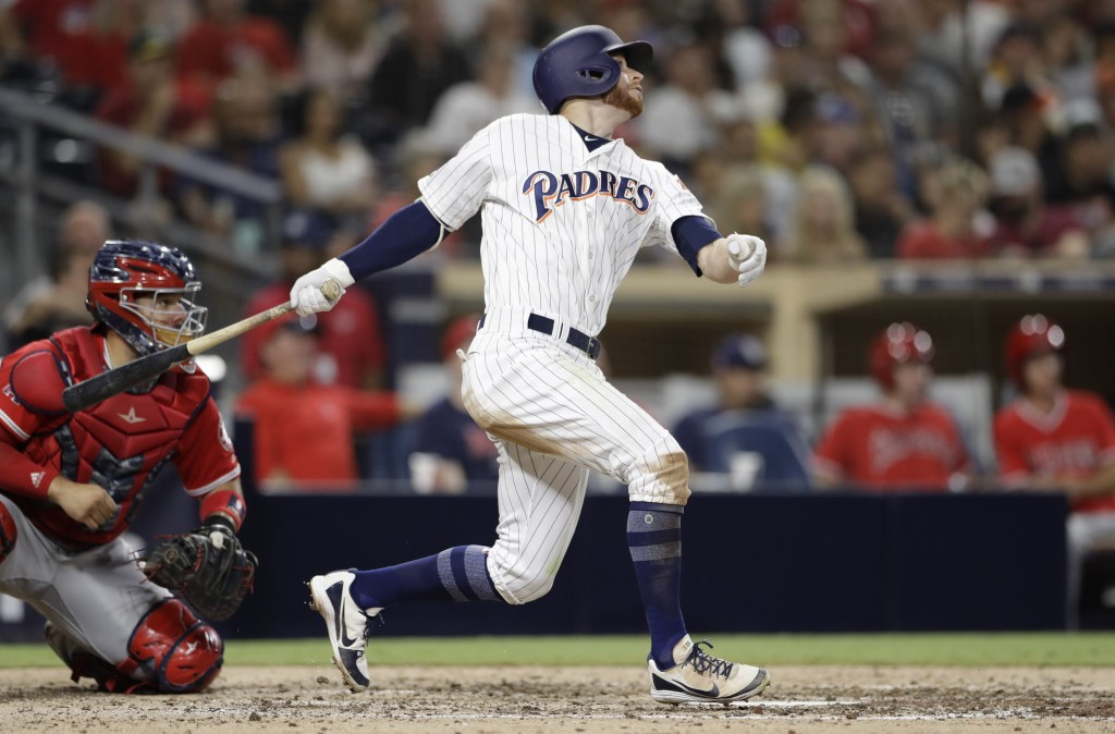 San Diego Padres' Cory Spangenberg watches his home run next to Los Angeles Angels catcher Rene Rivera during the seventh inning of a baseball game We...