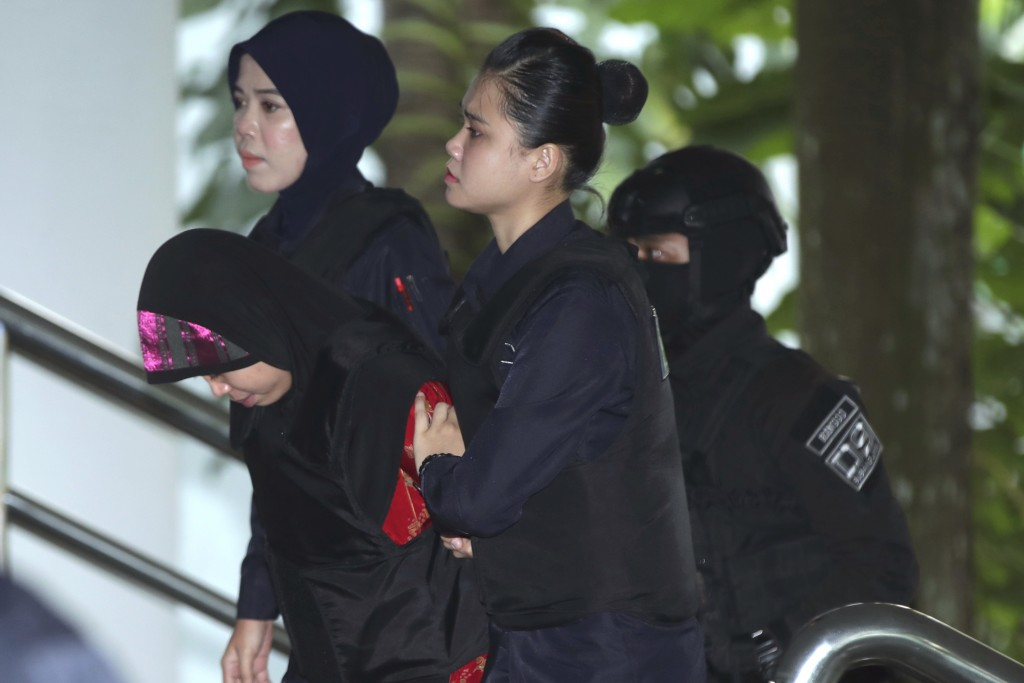Indonesian Siti Aisyah, left, is escorted by police as she arrives for a court hearing at Shah Alam High Court in Kuala Lumpur, Malaysia, Thursday, Au...