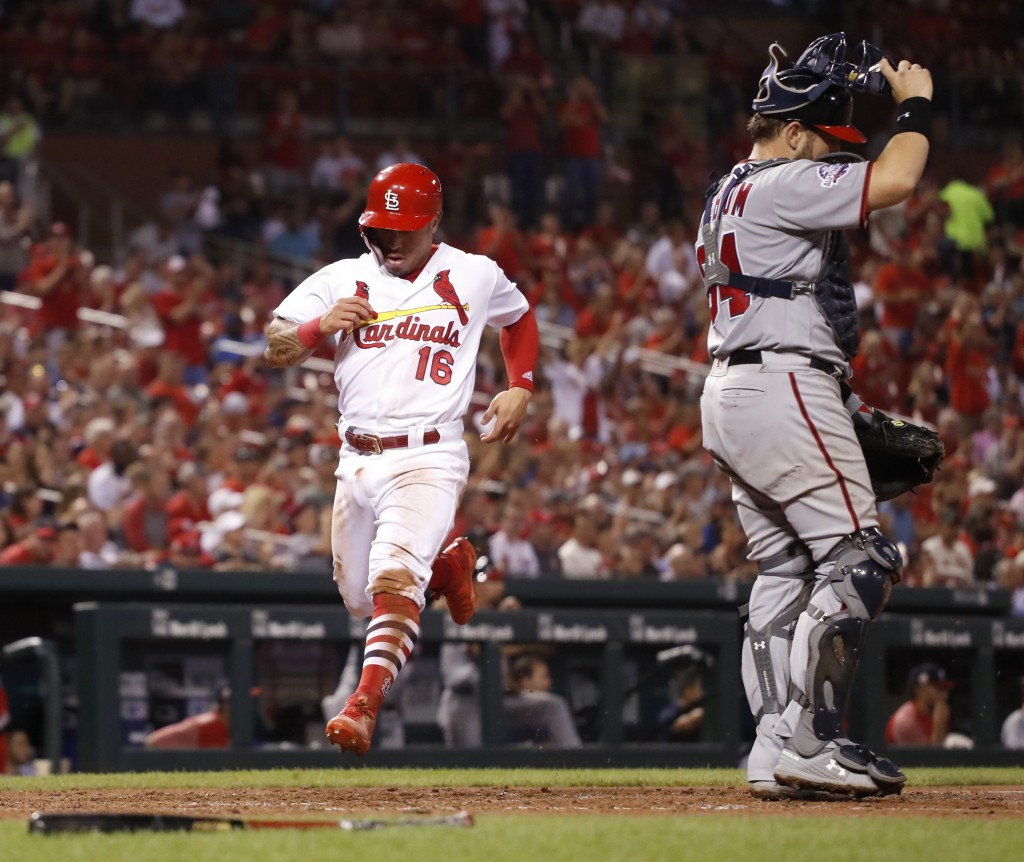 St. Louis Cardinals' Kolten Wong (16) scores past Washington Nationals catcher Spencer Kieboom during the seventh inning of a baseball game Wednesday,...