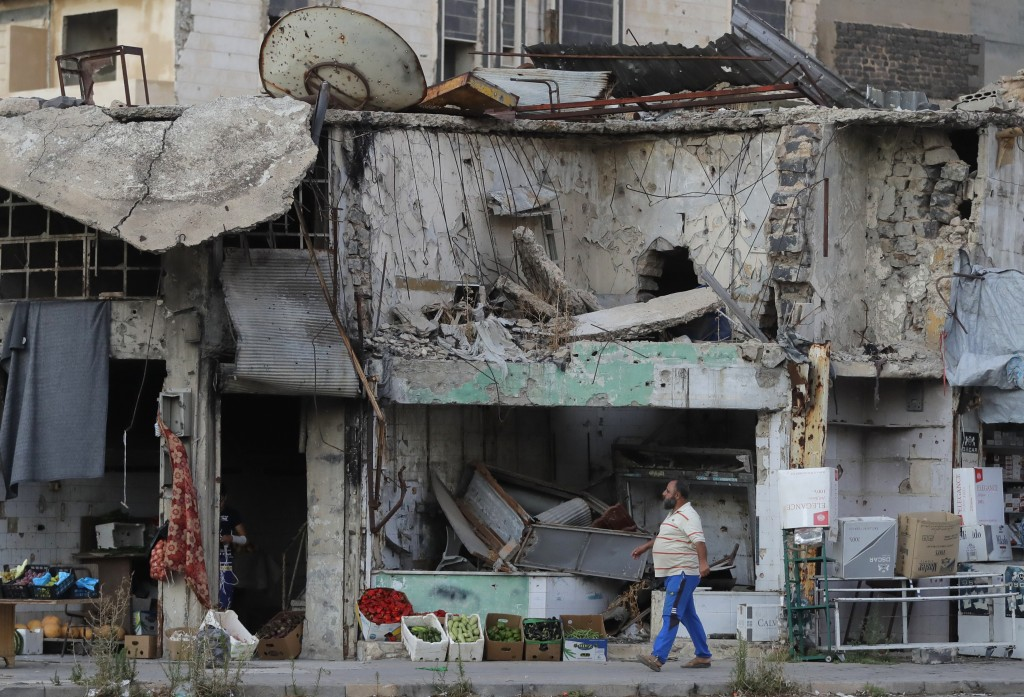 A man walks next to damaged buildings in the old town of Homs, Syria, Wednesday, Aug. 15, 2018. The Russian Defense Ministry said it is coordinating e...