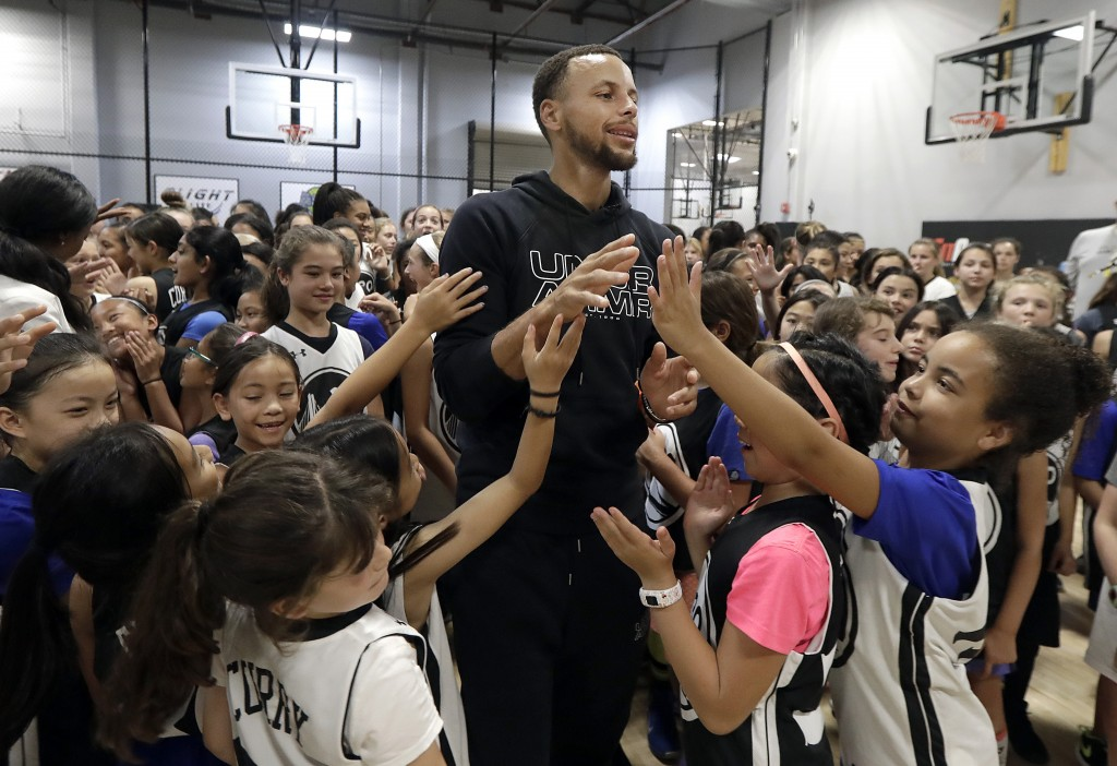 Golden State Warriors' Stephen Curry, center, greets basketball camp participants after taking a group photo at Ultimate Fieldhouse in Walnut Creek, C...