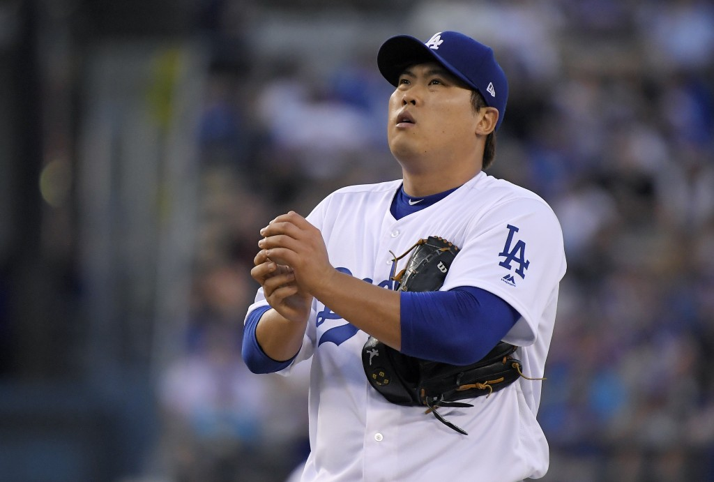 Los Angeles Dodgers starting pitcher Hyun-Jin Ryu rubs up the ball before pitching during the first inning of the team's baseball game against the San...