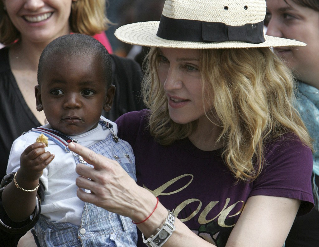 FILE- In this April 19, 2007 file photo, U.S. singer Madonna carries her Malawian adopted son David Banda in the village of Masekese, Malawi. The Quee...