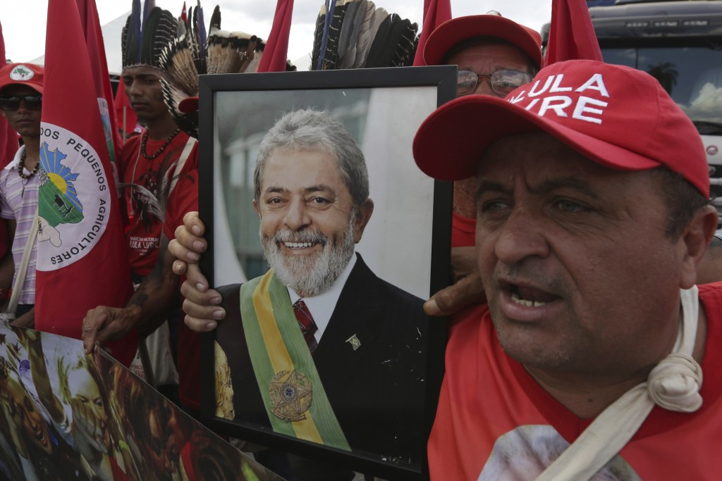 Supporters holding a photo of Brazil's jailed former president Luiz Inacio Lula da Silva takes part in the Free Lula March, in Brasilia, Brazil, Wedne...