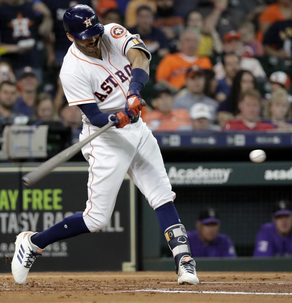Houston Astros' Carlos Correa hits a three-run double against the Colorado Rockies during the first inning of a baseball game Wednesday, Aug. 15, 2018...