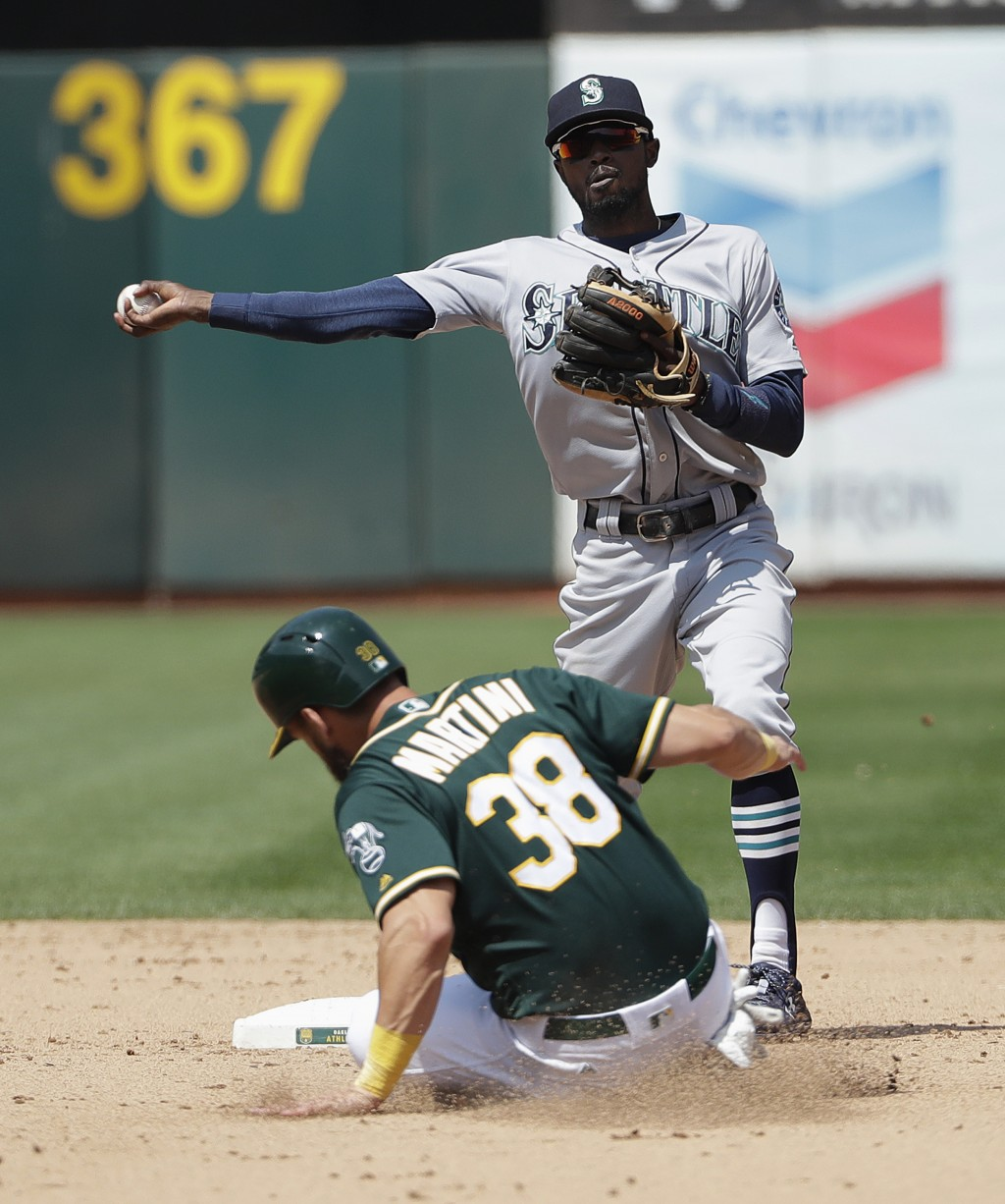 Seattle Mariners' Dee Gordon, top, throws to first base after forcing out Oakland Athletics' Nick Martini (38) on a double play ball hit into by Jed L...
