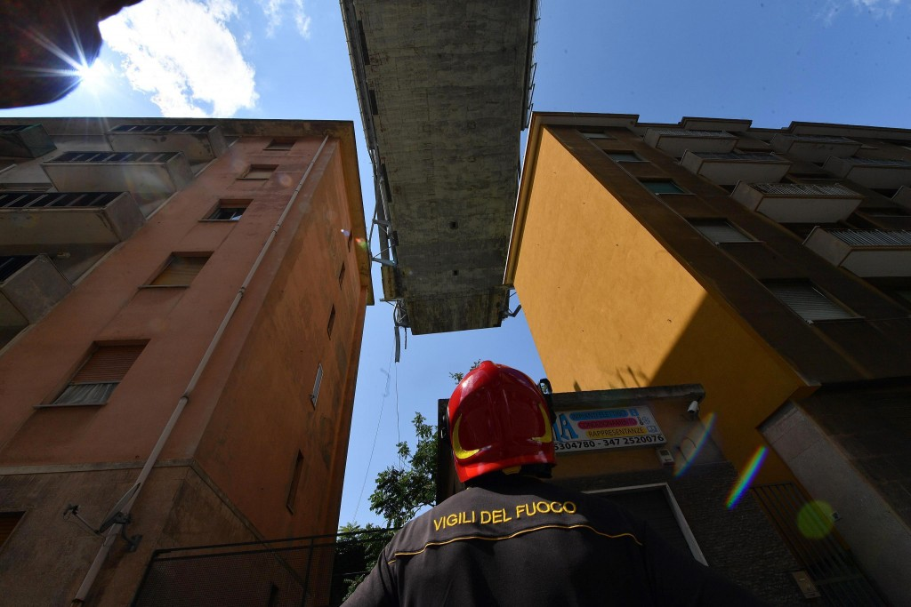 A firefighter looks up at the partially collapsed Morandi highway bridge, in between buildings, in Genoa, Italy, Thursday, Aug. 16, 2018. The death to...