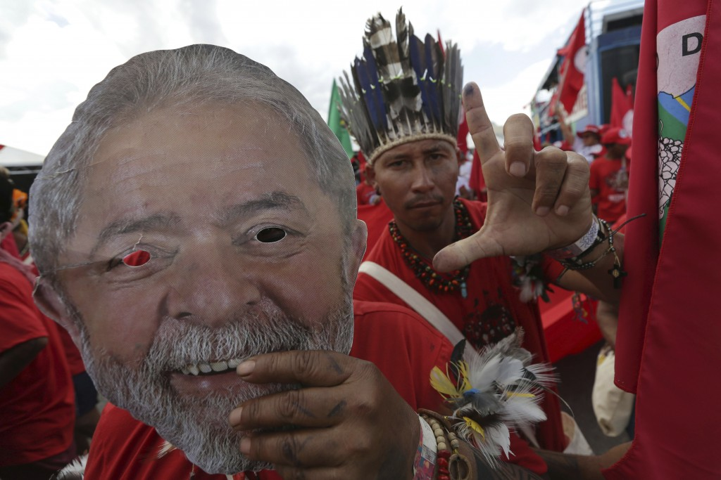 Supporters holding masks of Brazil's jailed former president Luiz Inacio Lula da Silva take part in the Free Lula March, in Brasilia, Brazil, Wednesda...
