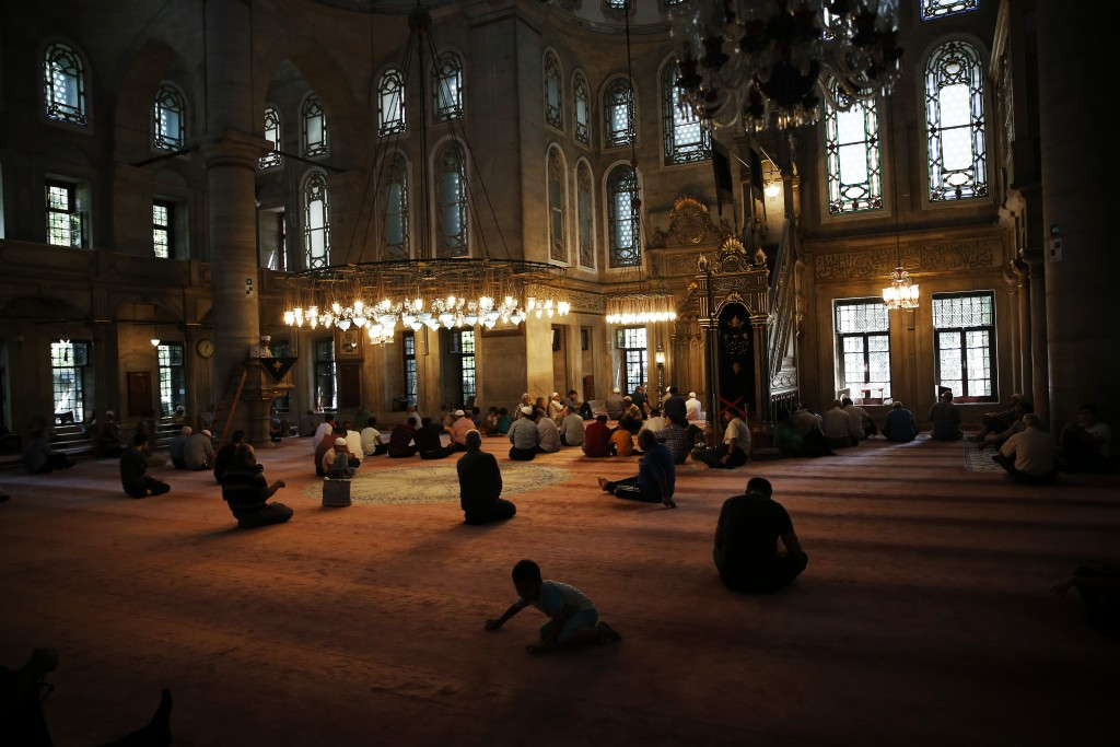 People sit in a mosque in Istanbul before of prayers on Wednesday, Aug. 15, 2018. Turkey is deeply divided between Erdogan's pious Muslim base and sec...