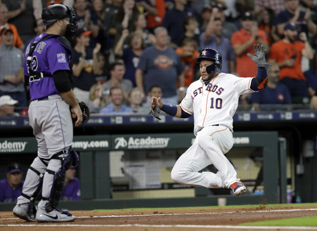 Houston Astros' Yuli Gurriel (10) scores as Colorado Rockies catcher Chris Iannetta looks toward the outfield during the first inning of a baseball ga...