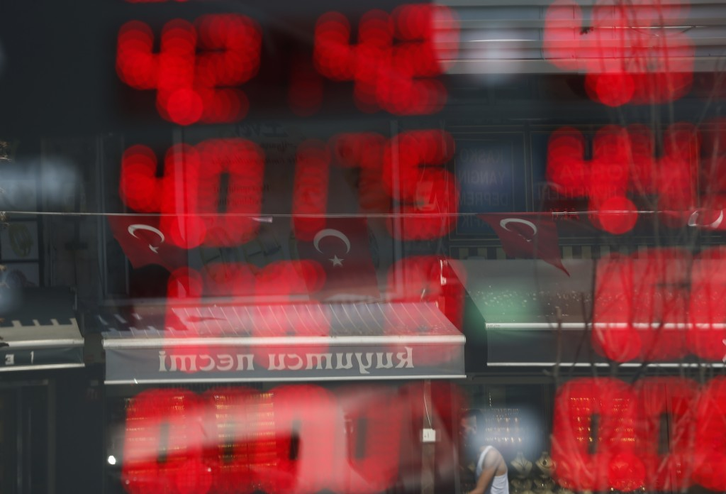 Turkish flags are reflected in the window of a currency exchange shop, displaying current rates, in Istanbul, Wednesday, Aug. 15, 2018. Many economic ...
