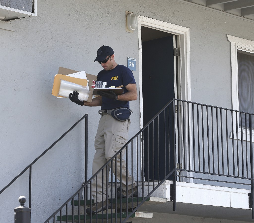 A federal agent removes items from an apartment following the arrest of a 45-year-old Iraqi refugee, Omar Ameen, Wednesday, Aug. 15, 2018, in Sacramen...