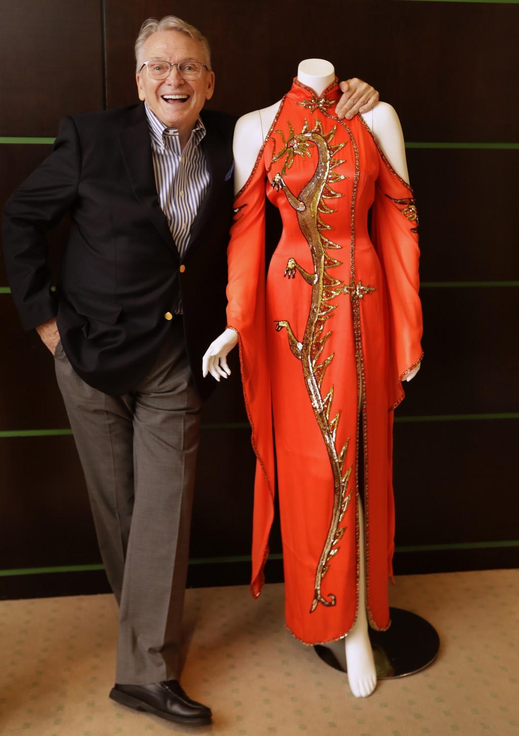Fashion and Costume Designer Bob Mackie poses with one of his iconic designs, a scarlet red satin gown worn by Cher in 1975, in London, Thursday, Aug....