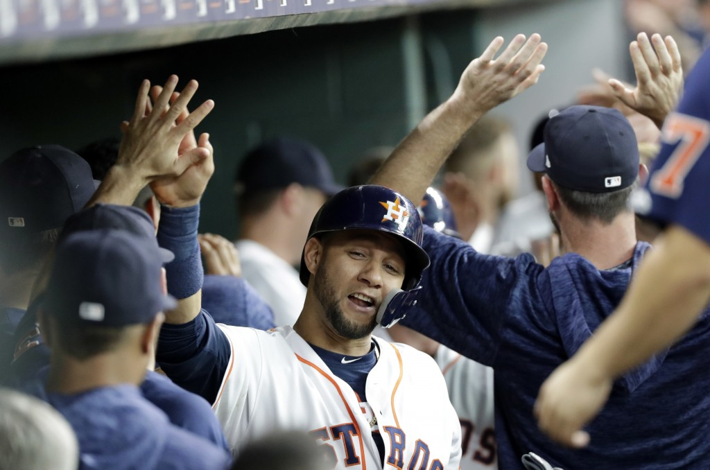 Houston Astros' Yuli Gurriel celebrates with teammates in the dugout after scoring against the Colorado Rockies during the first inning of a baseball ...