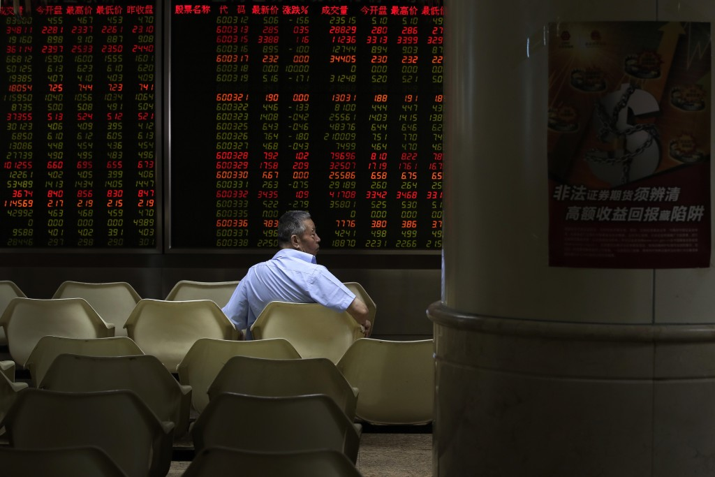 A man sits in front of an electronic board displaying stock prices at a brokerage house in Beijing, Thursday, Aug. 16, 2018. Asian shares are falling ...