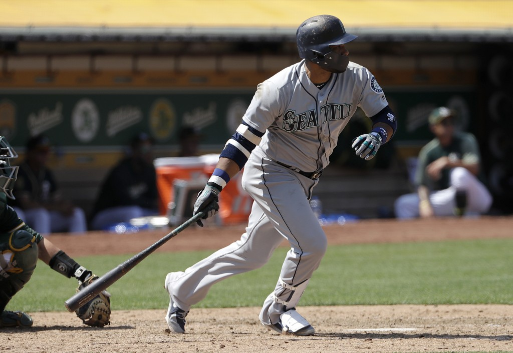 Seattle Mariners' Robinson Cano hits a single against the Oakland Athletics during the eleventh inning of a baseball game in Oakland, Calif., Wednesda...