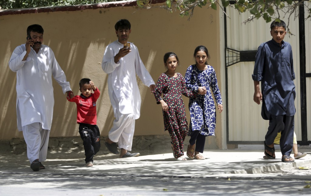 Families leave their houses during a nearby clash between insurgents and security forces in Kabul, Afghanistan, Thursday, Aug. 16, 2018. Gunmen besieg...