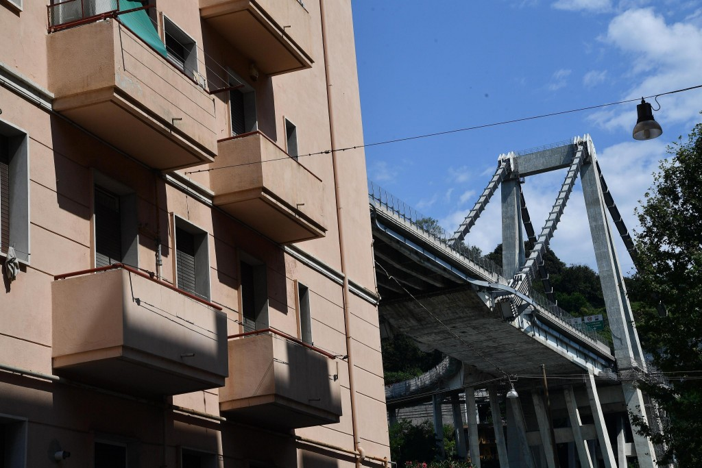 Buildings stand next to the partially collapsed Morandi highway bridge in Genoa, Italy, Thursday, Aug. 16, 2018. The death toll from the collapse of a...
