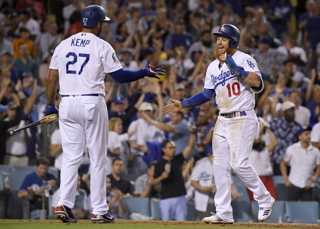 Los Angeles Dodgers' Justin Turner, right, celebrates with Matt Kemp after scoring on a double by Manny Machado during the seventh inning of a basebal...