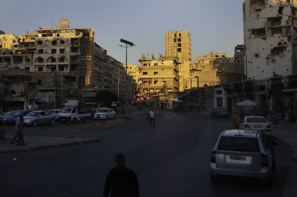 People walk amid damaged buildings in the old city of Homs, Syria, Wednesday, Aug. 15, 2018. The Russian Defense Ministry said Wednesday it is coordin...