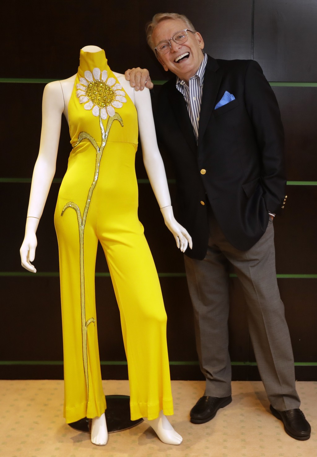 Fashion and Costume Designer Bob Mackie poses with one of his iconic designs, a marigold jersey jumpsuit worn by Cher between 1971-1976, in London, Th...