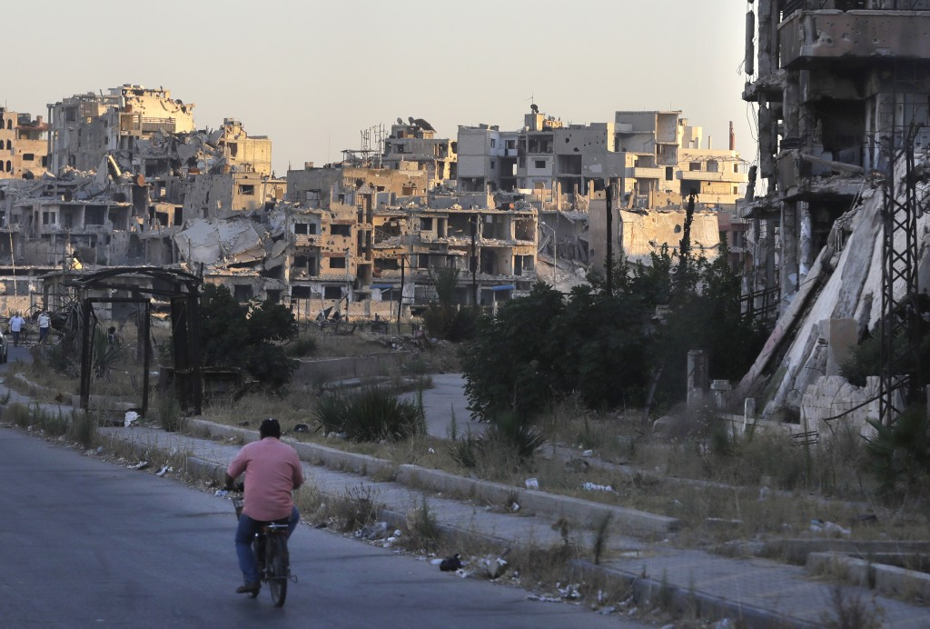 A man rides his bicycle by damaged buildings in the old town of Homs, Syria, Wednesday, Aug. 15, 2018. The Russian Defense Ministry said it is coordin...