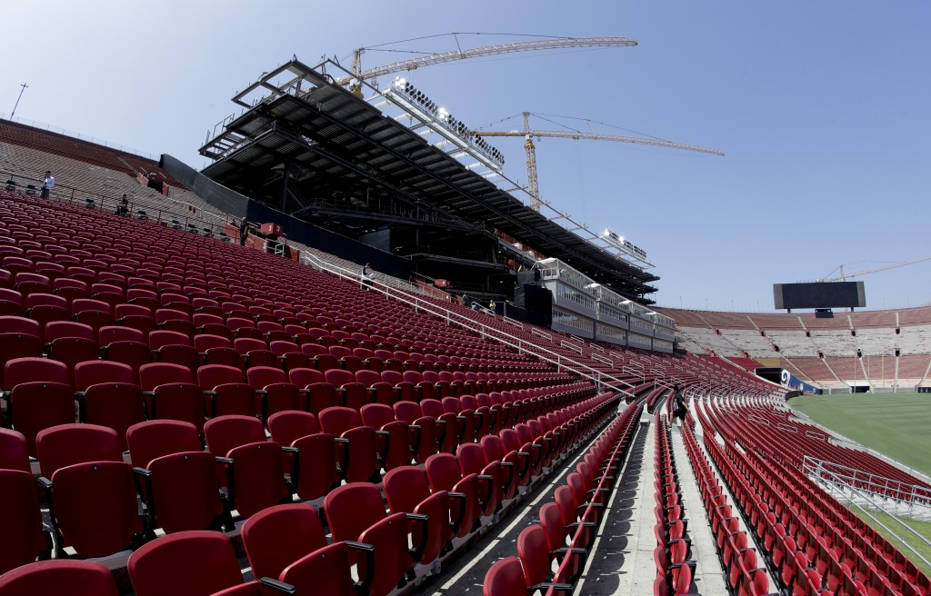 Stadium personnel walk near a new section of seat at the Los Angeles Memorial Coliseum in Los Angeles, Wednesday, Aug. 15, 2018. The 95-year-old Colis...