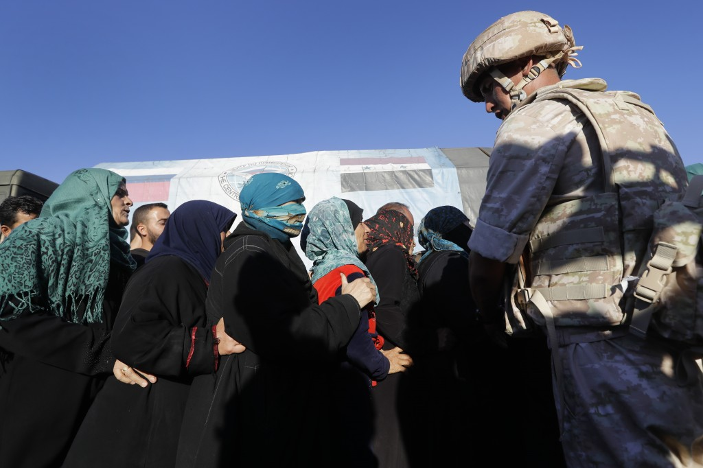 Russian soldier keeps watch as local residents receive humanitarian aid in the town of Rastan, Syria, Wednesday, Aug. 15, 2018. The Russian Defense Mi...