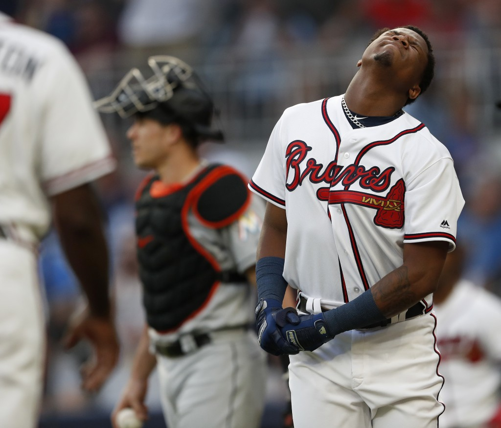 Atlanta Braves' Ronald Acuna Jr., right, reacts after being hit by a pitch from Miami Marlins'Jose Urena during the first inning of a baseball game We...