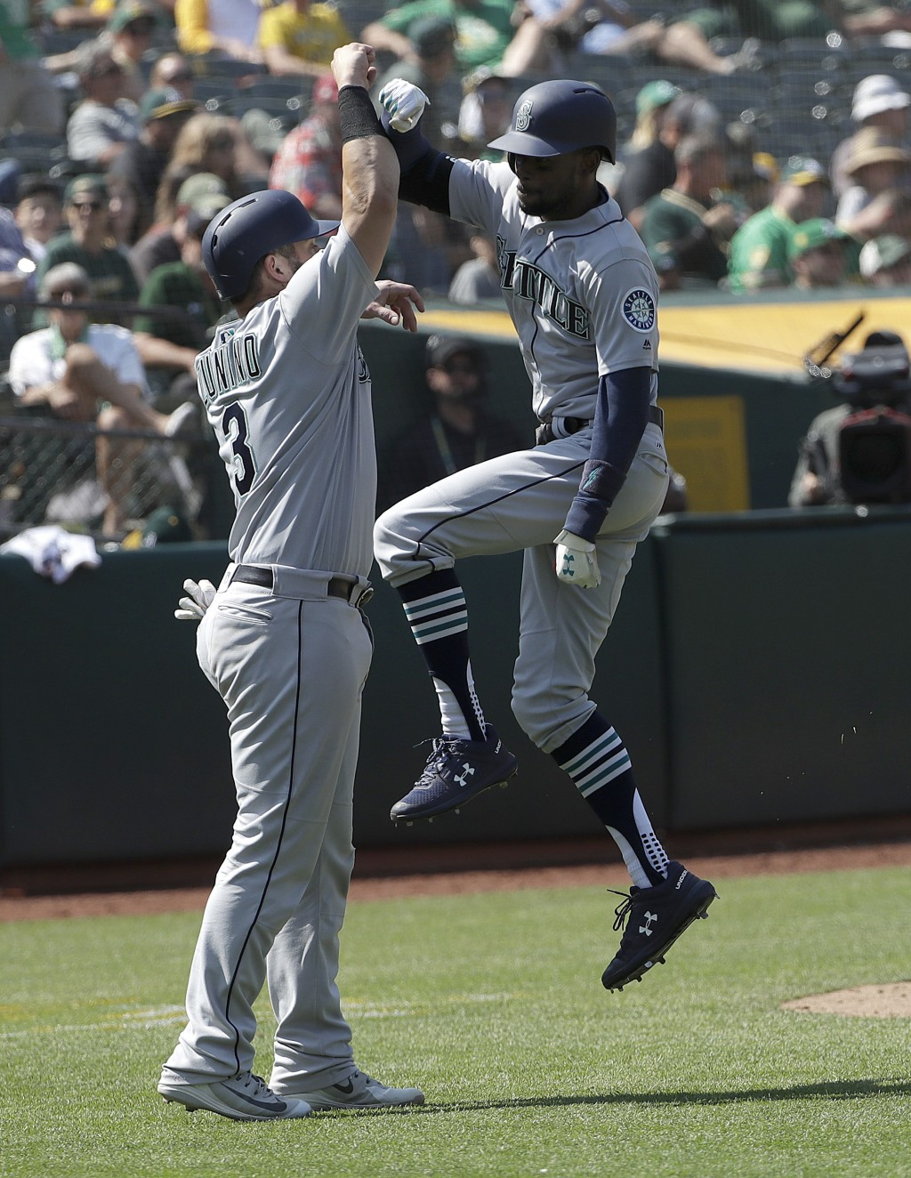 Seattle Mariners' Dee Gordon, right, celebrates after hitting a two-run home run that scored Mike Zunino, left, against the Oakland Athletics during t...