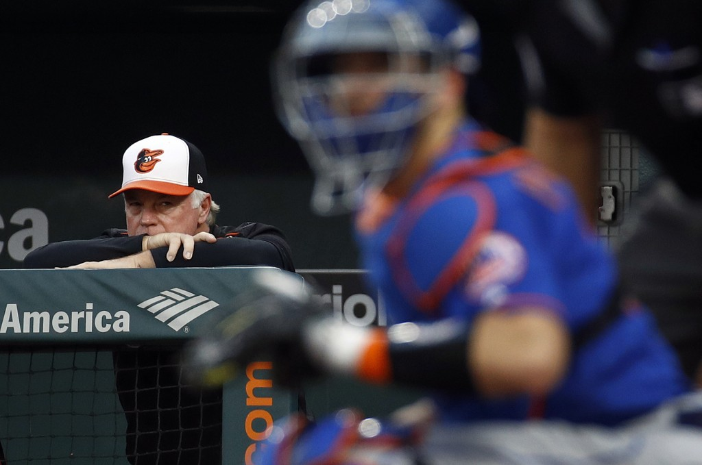 Baltimore Orioles manager Buck Showalter watches from the dugout, with New York Mets catcher Kevin Plawecki in the foreground, during the first inning...