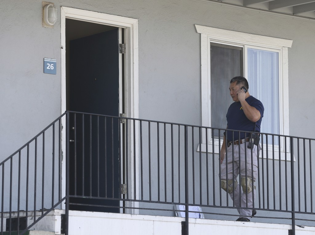 A federal agent makes a call outside the apartment following the arrest of a 45-year-old Iraqi refugee, Omar Ameen, Wednesday, Aug. 15, 2018, in Sacra...