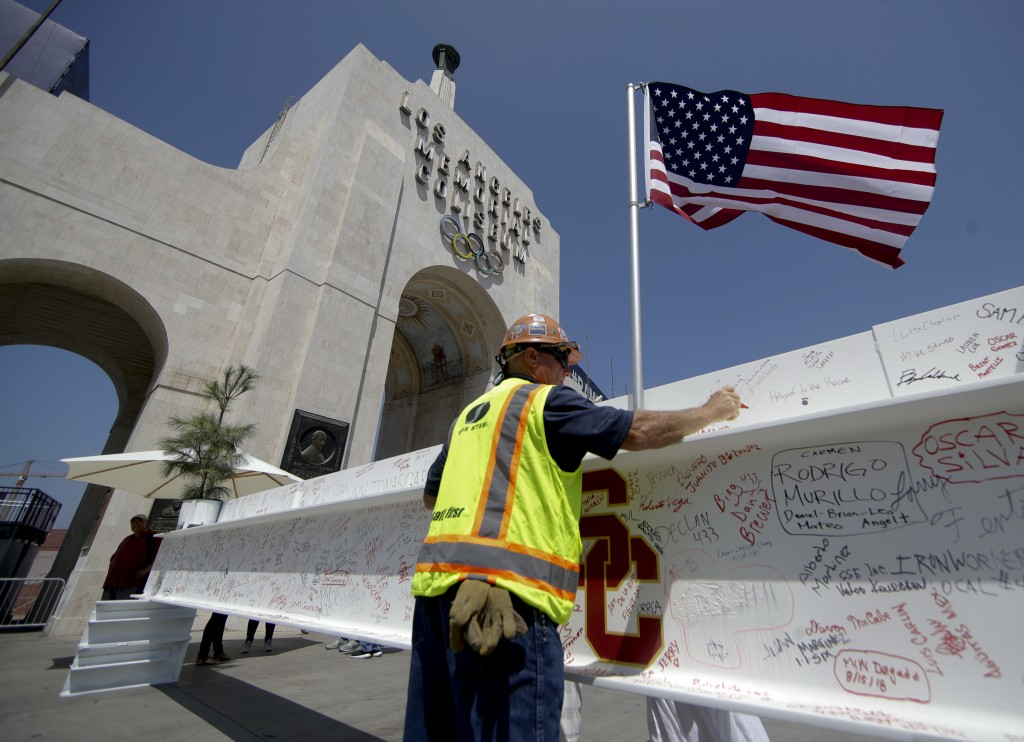 Chris Ahrens, steel worker signs the final beam in front of the Los Angeles Memorial Coliseum in Los Angeles, Wednesday, Aug. 15, 2018. Although the 9...