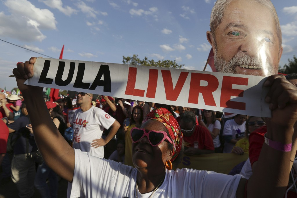 """A supporter of jailed, former President Luiz Inacio Lula da Silva, holds a sign that reads in Portuguese: """"Free Lula"""" at a march in Brasilia, Brazil, ..."""