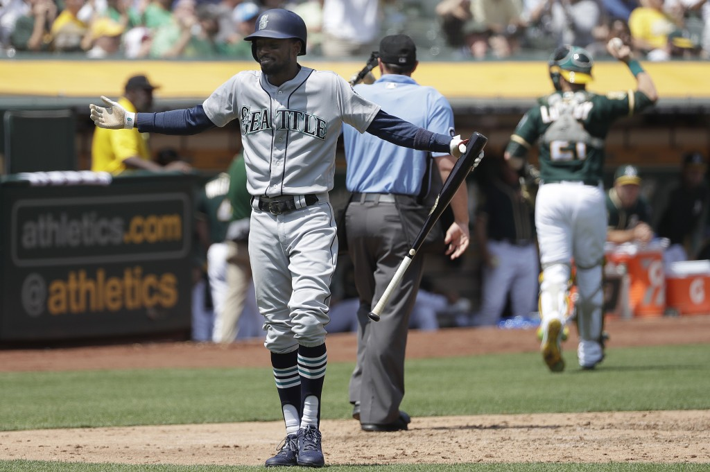 Seattle Mariners' Dee Gordon reacts after striking out against the Oakland Athletics during the fifth inning of a baseball game in Oakland, Calif., We...