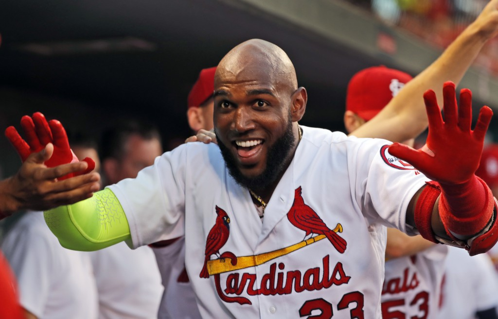 St. Louis Cardinals' Marcell Ozuna is congratulated by teammates after hitting a solo home run during the second inning of the team's baseball game ag...