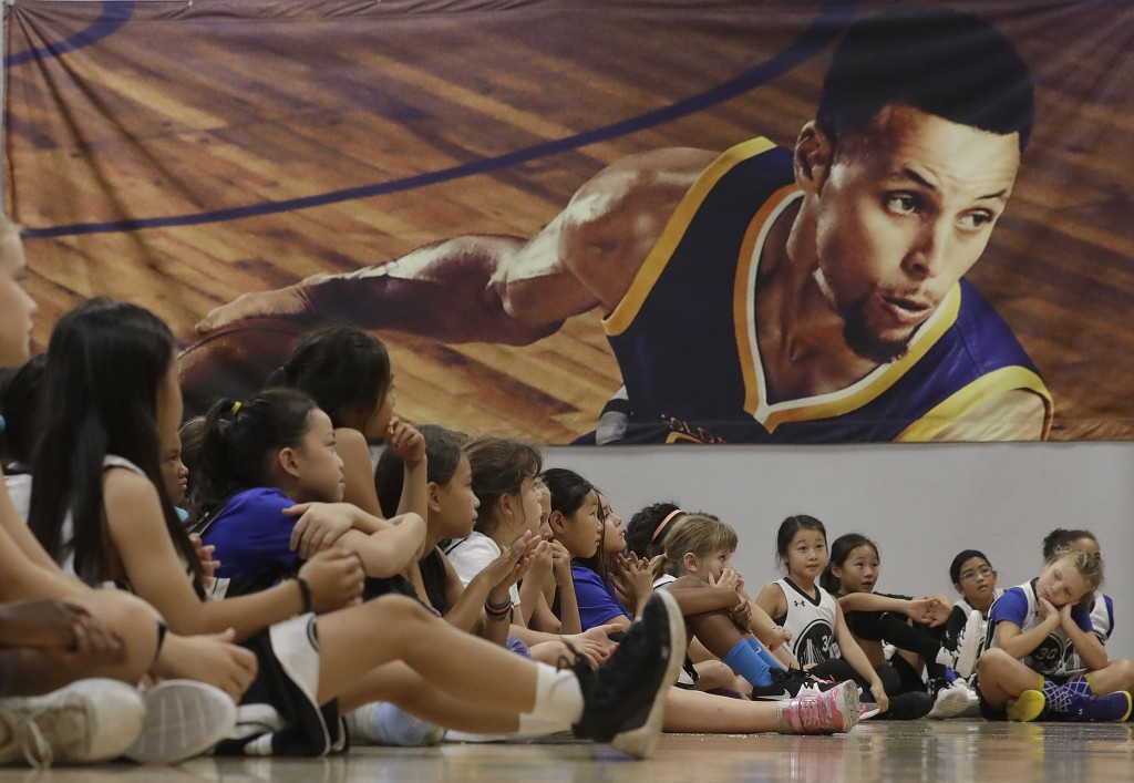 An image of Golden State Warriors' Stephen Curry, top, is displayed ;behind basketball camp participants as they listen to speakers on a panel for wom...