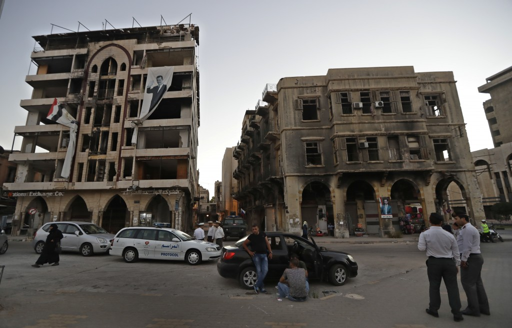 People congregate at the square, with damaged buildings in the background, in the old town of Homs, Syria, Wednesday, Aug. 15, 2018. The Russian Defen...
