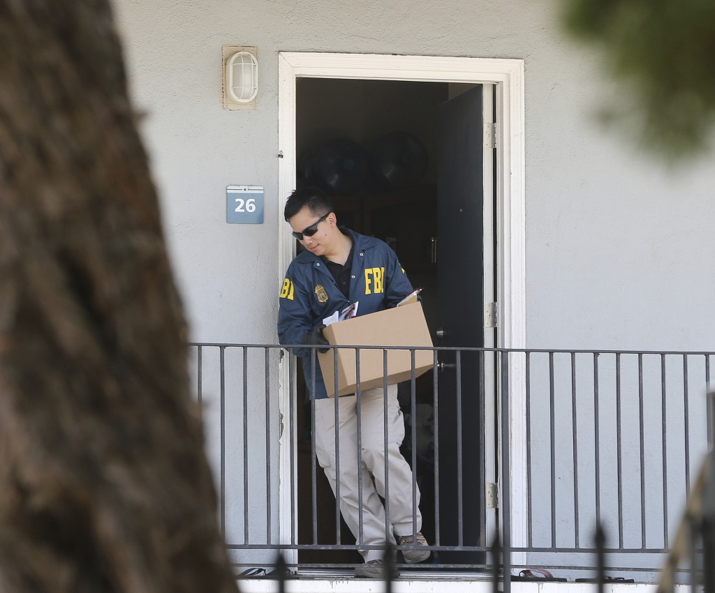 A federal agent removes items from an apartment following the arrest of Omar Ameen, Wednesday, Aug. 15, 2018, in Sacramento, Calif. Ameen, a 45-year-o...