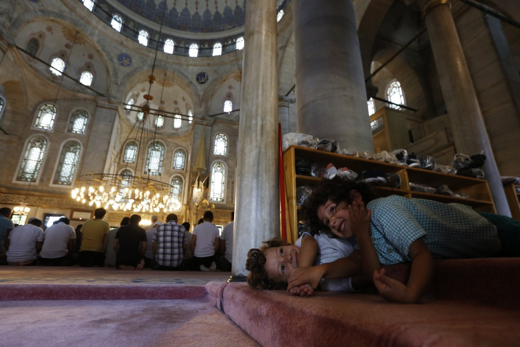 Children play in a mosque before prayers in Istanbul, Turkey on Wednesday, Aug. 15, 2018. Turkey is deeply divided between Erdogan's pious Muslim base...