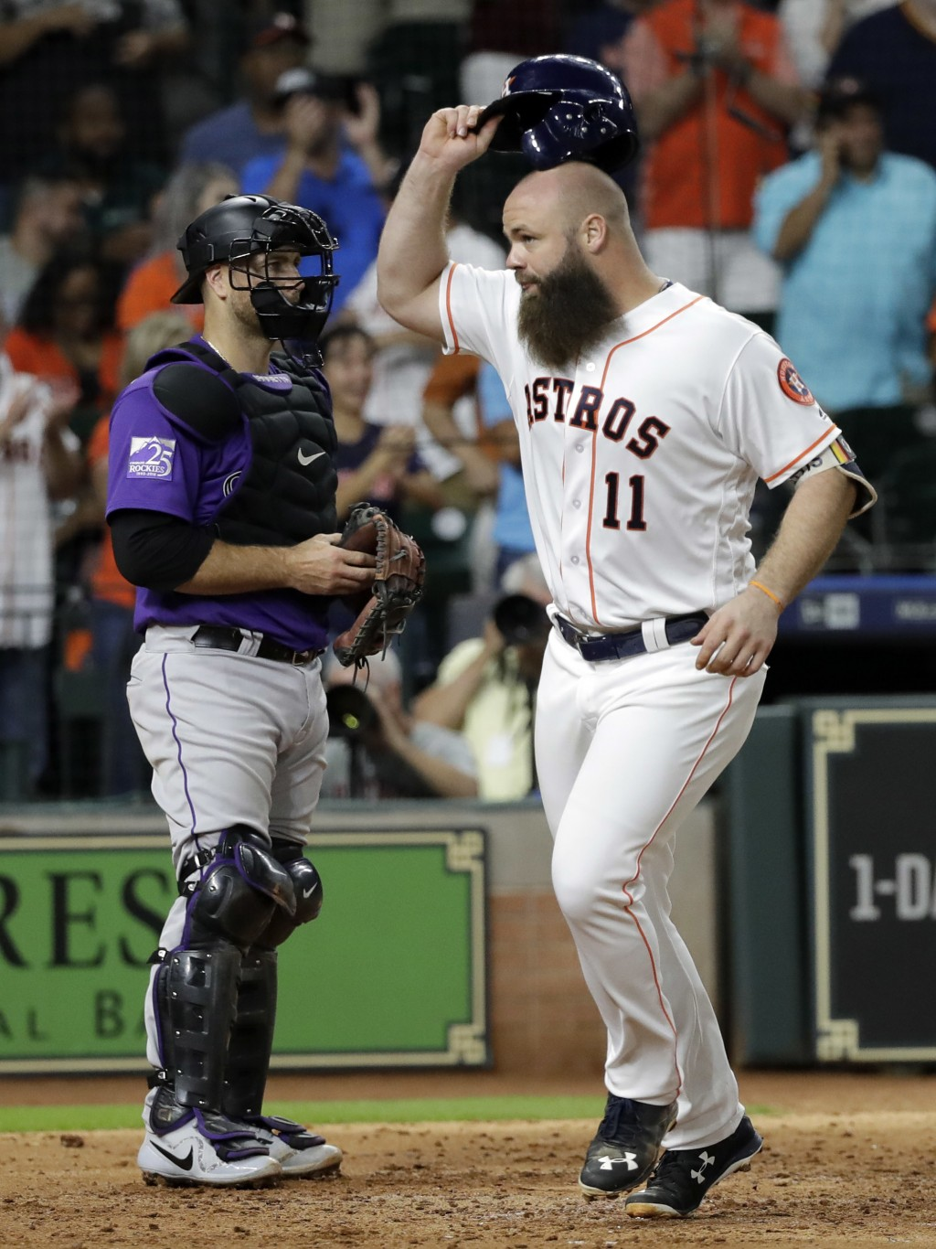 Houston Astros' Evan Gattis (11) celebrates after hitting a home run as Colorado Rockies catcher Chris Iannetta stands near home plate during the fift...