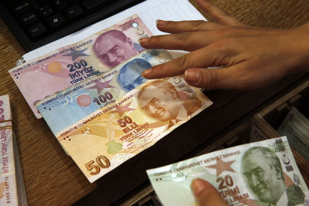 FILE- In this Wednesday, Aug. 15, 2018, file photo a worker at a currency exchange shop exhibits Turkish lira banknotes bearing pictures of modern Tur...