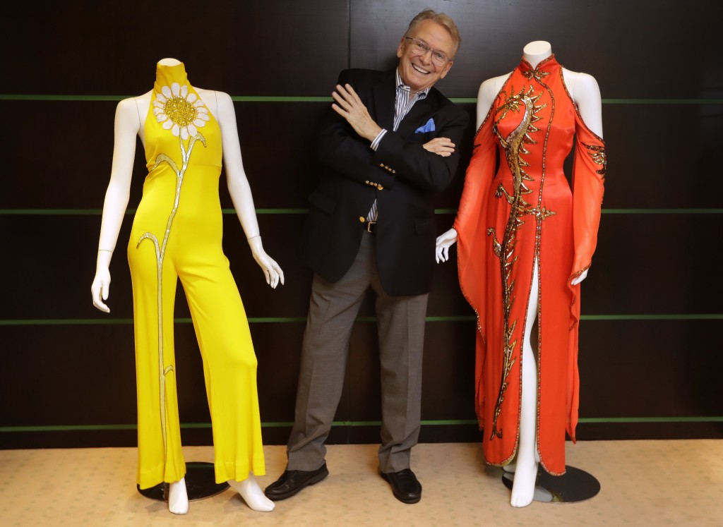 Fashion and Costume Designer Bob Mackie poses with two of his iconic designs, a scarlet red satin gown worn by Cher in 1975, right, and a marigold jer...