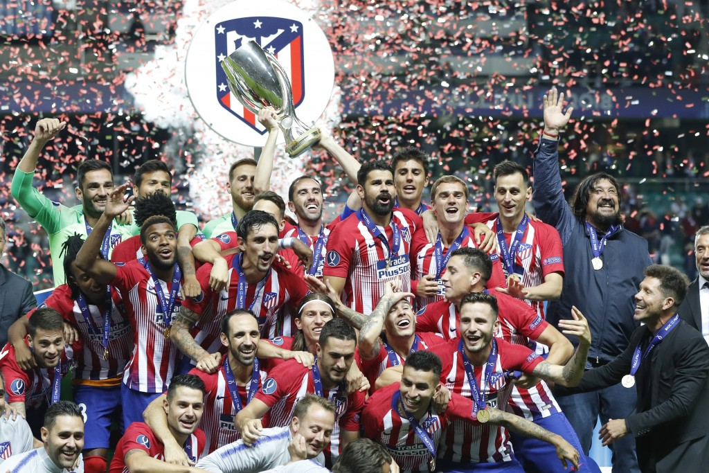 Atletico's team members celebrate with trophy after the UEFA Super Cup final soccer match between Real Madrid and Atletico Madrid at the Lillekula Sta...